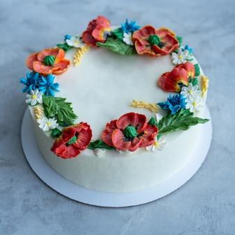 Ciasto z kremowym lukrem ozdobione kwiatami kremu