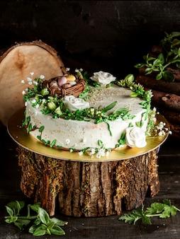 Ciasto z kremowymi jajkami czekoladowymi w gnieździe i róże