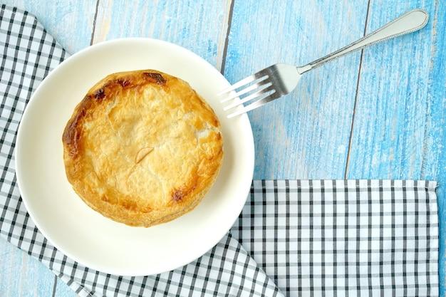 Ciasto z kurczakiem i grzybami podawane na niebieskim drewnianym stole z widelcem. żywność martwa.