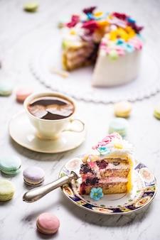 Ciasto z kwiatów marcepanu, makaroniki i filiżanka czarnej kawy.