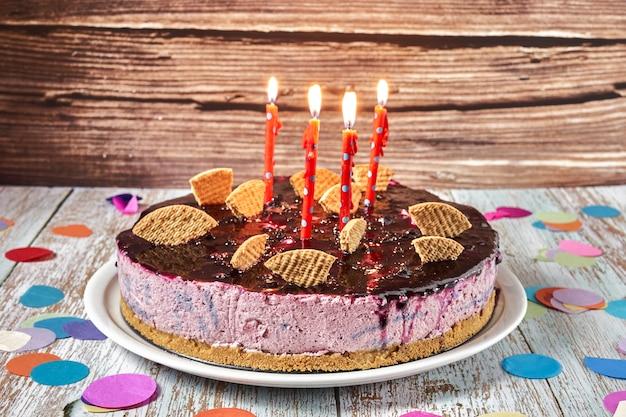 Ciasto z musem z owoców leśnych ozdobione kawałkami biszkoptu i czterema świeczkami