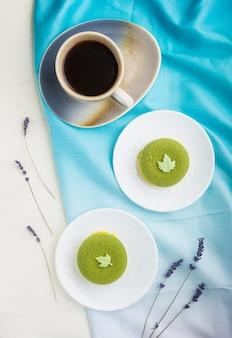 Ciasto z musem zielonym z kremem pistacjowym i filiżanką kawy na białej drewnianej powierzchni. widok z góry, z bliska.