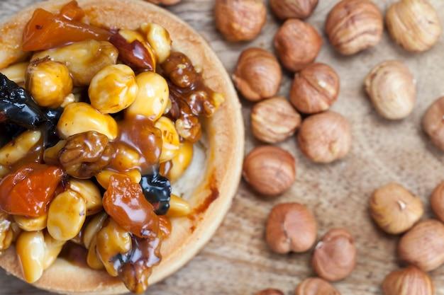 Ciasto z orzechami i bakaliami w karmelu, mała okrągła tarta z różnymi nadzieniami, chrupiąca tarta z orzechami laskowymi, orzeszkami ziemnymi i innymi dodatkami
