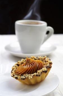 Ciasto z orzechami i filiżanką gorącej kawy o małej głębi ostrości