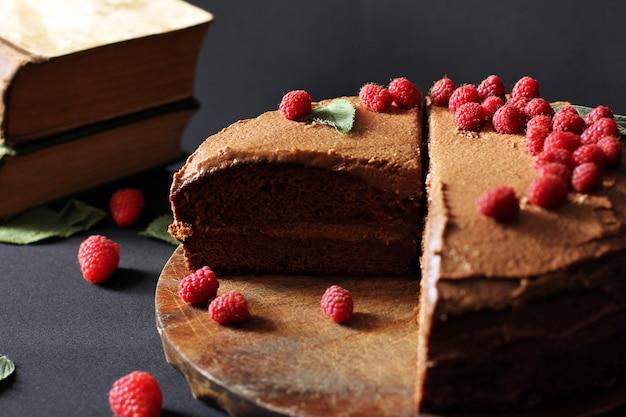 Ciasto z pragi. ciasto czekoladowe z malinami i książkami. ciasto na ciemnym tle