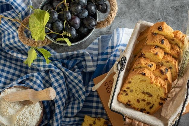 Ciasto z rodzynkami, miska mąki i winogron na marmurowej powierzchni