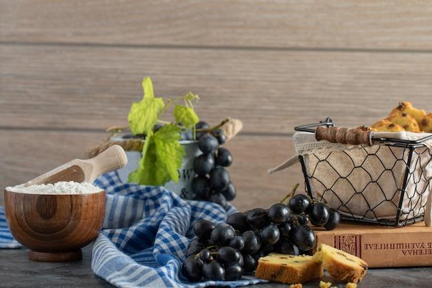 Ciasto z rodzynkami, winogrona i miska na mące na marmurowym stole
