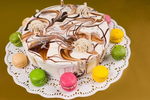 Ciasto z różnymi czekoladowymi ozdobami, w pobliżu makaroników, na żółtym tle