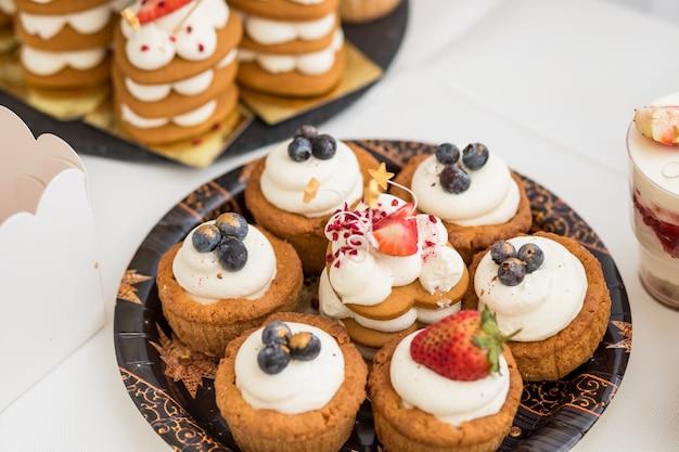Ciasto z różnymi jagodami i bezami na stojaku. ciasta, deser z jagodami, batonik na imprezę