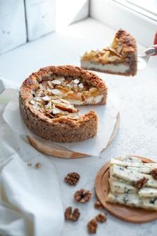Ciasto z serem pleśniowym, gruszkami i migdałami, całe okrągłe na talerzu na białym stole.