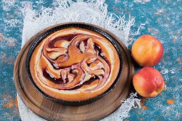 Ciasto z syropem truskawkowym z brzoskwiniami wokół.
