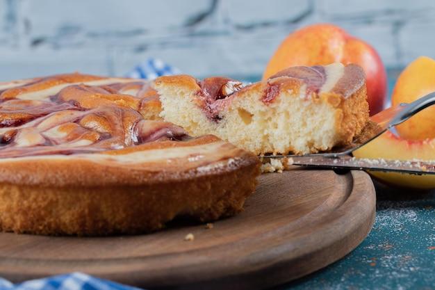 Ciasto z syropem truskawkowym z żółtymi brzoskwiniami wokół.