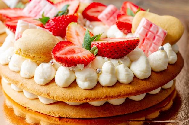 Ciasto z truskawkami, batonami różowej mlecznej czekolady, srebrną posypką, kremem waniliowym i ciasteczkami serduszka z bliska.
