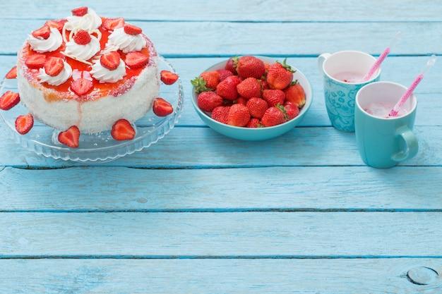Ciasto z truskawkami na niebieskim drewnianym stole