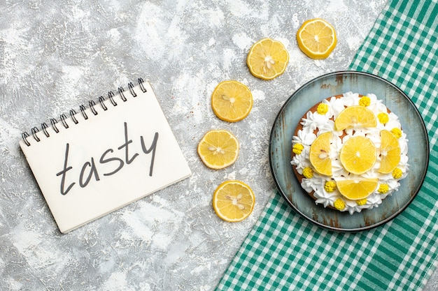 Ciasto z widokiem z góry z białą śmietaną i plasterkami cytryny na talerzu na zielonym białym obrusie w kratkę
