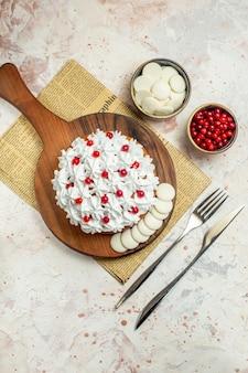 Ciasto z widokiem z góry z białym kremem cukierniczym na drewnianej desce na widelcu i nożem obiadowym jagody i biała czekolada w miskach