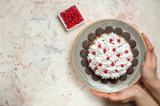 Ciasto z widokiem z góry z kremem cukierniczym i czekoladą w kobiecej dłoni jagody w misce