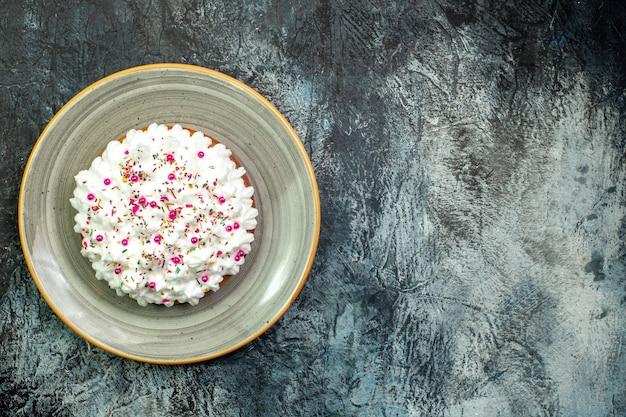 Ciasto z widokiem z góry z kremem cukierniczym na szarym okrągłym talerzu na szarym stole z miejscem na kopię