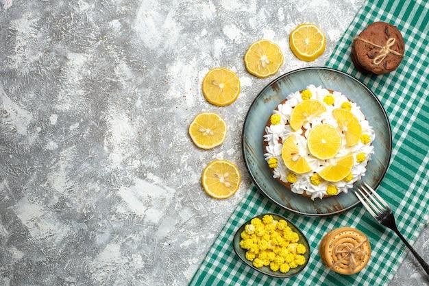 Ciasto z widokiem z góry z kremem do ciasta i widelcem cytrynowym na półmisku ciasteczka cukierki w misce na zielonym białym obrusie w kratkę