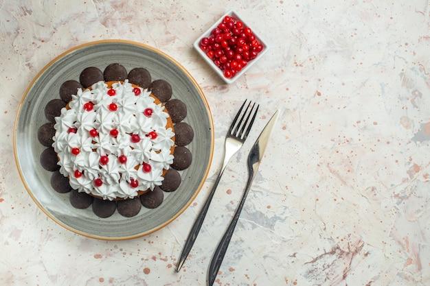 Ciasto z widokiem z góry z kremem do ciasta i widelcem czekoladowym i jagodami noża obiadowego w misce