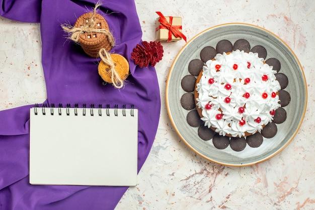 Ciasto z widokiem z góry z kremem z białego ciasta na owalnym talerzu ciasteczka przewiązane sznurkiem zeszyt na fioletowym szalu