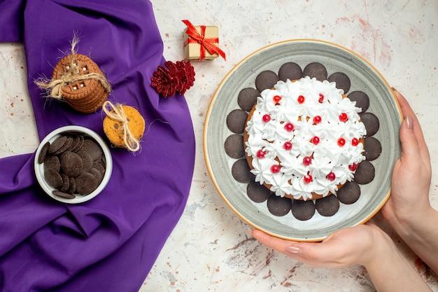 Ciasto z widokiem z góry z kremem z białego ciasta na talerzu w dłoniach kobiety ciasteczka związane sznurkiem miska czekolady na fioletowym shaw