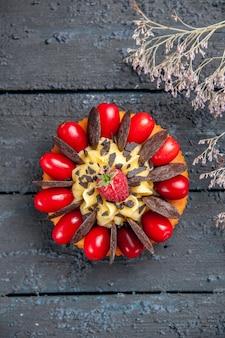 Ciasto z widokiem z góry z owocami dereń i czekoladą na ciemnej powierzchni drewnianej