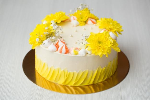Ciasto z żółtymi plamami, żółtymi chryzantemami i bezą