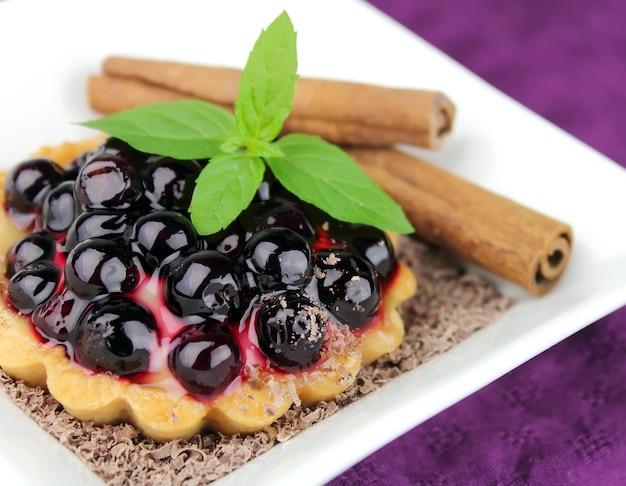 Ciasto ze świeżymi jagodami, cynamonem i miętą na białym tle