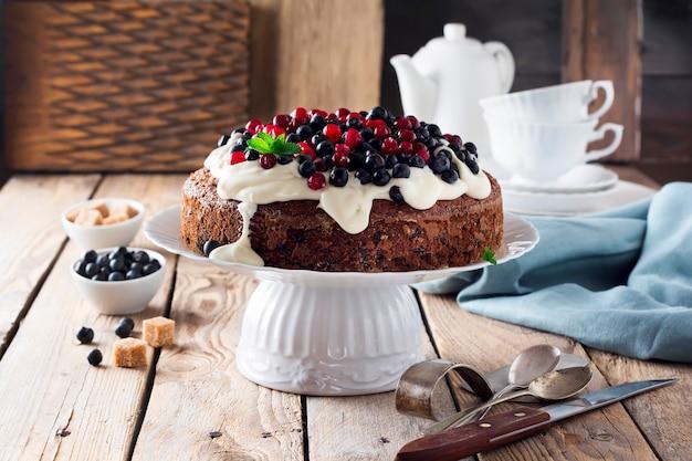 Ciasto ze świeżymi jagodami i śmietaną na starej drewnianej powierzchni