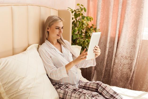 Ciąża, technologia, ludzie i koncepcja oczekiwania - szczęśliwa kobieta w ciąży z komputerem typu tablet w łóżku w domu