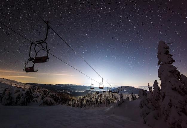 Cicha ścieżka kolejki unosiła się nad zaśnieżonym ośrodkiem narciarskim wśród jodły na tle rozgwieżdżonego nieba. niezapomniana koncepcja ferii zimowych. copyspace