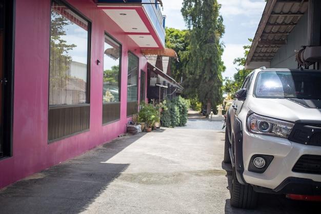 Cicha ulica z cieniem i zaparkowanym samochodem w upalny słoneczny dzień. wioska azjatycka.