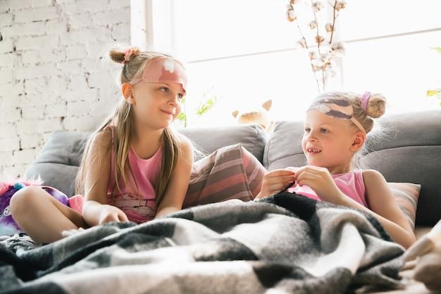 Ciche małe dziewczynki budzące się w sypialni w uroczej piżamie, domowym stylu i komforcie