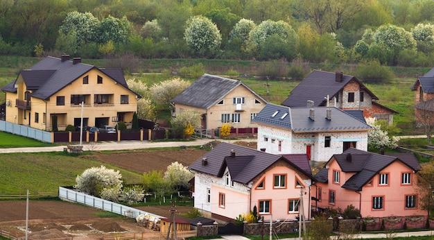Ciche podmiejskie osiedle mieszkaniowe. ulica z nowymi nowoczesnymi wygodnymi domkami z cegły z podwórkami i kwitnącymi ogrodami na pięknym zielonym lesie. inwestycje w koncepcję nieruchomości.