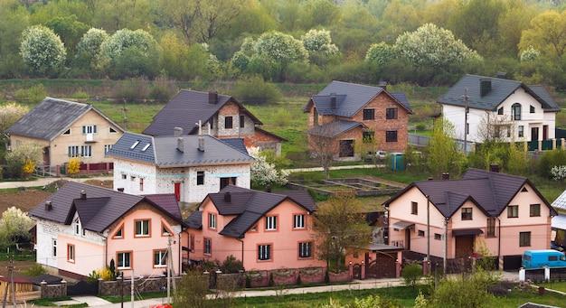 Ciche podmiejskie osiedle mieszkaniowe. ulica z nowymi nowoczesnymi wygodnymi domkami z cegły z podwórkami i kwitnącymi ogrodami na scenie pięknego zielonego lasu. inwestycje w koncepcję nieruchomości.