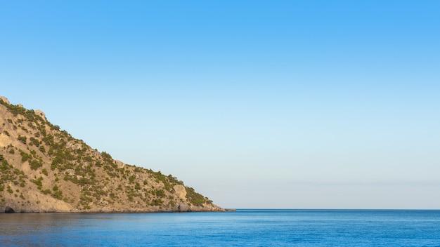 Ciche, spokojne błękitne morze i zalesione zbocze góry, zatoka vesele w gminie sudak na krymie