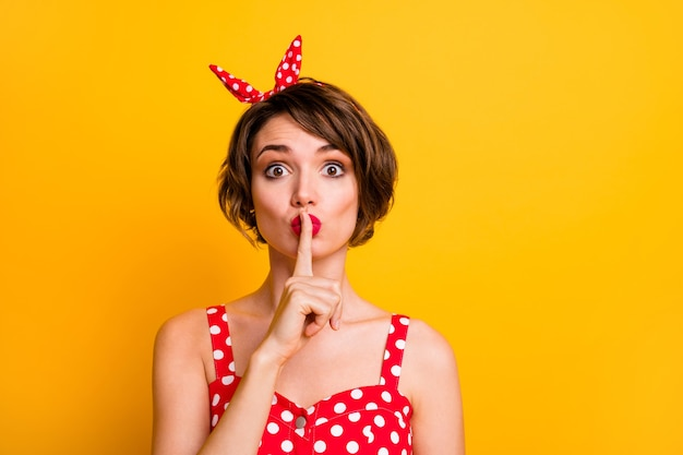 Cicho, cicho! funky słodka słodka dziewczyna zapytaj, nie udostępniaj tajnej poufnej nowości, umieść usta z palcem wskazującym na czerwoną sukienkę w stylu vintage odizolowaną na jasnej ścianie