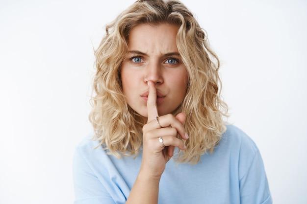 """Cicho, nie możesz tego powiedzieć. portret niezadowolonej blond dziewczyny z krótką fryzurą i niebieskimi oczami, patrzącej z przerażeniem, marszczącej brwi, mówiącej """"cii"""" z palcem wskazującym na ustach, mówiącej """"zachowaj tajemnicę"""" nad białą ścianą"""