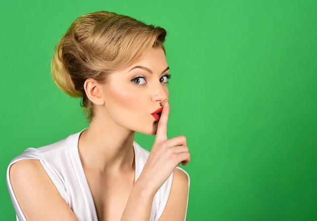 Cicho, urocza kobieta, która w tajemnicy trzyma palec na ustach, pokazuje shh znak atrakcyjna kobieta w bieli