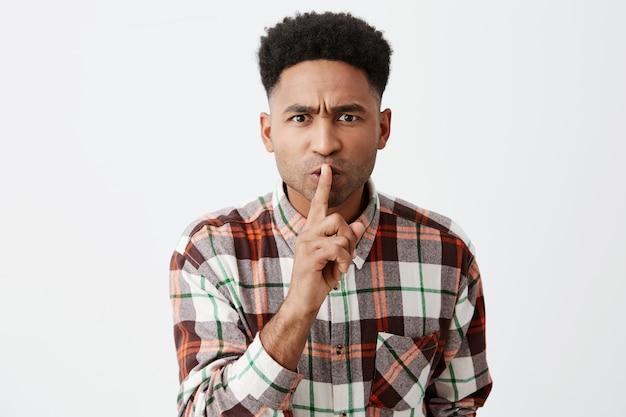 Cicho. zbliżenie poważnego młodego pięknego, ciemnoskórego mężczyzny z fryzurą afro w swobodnej kraciastej koszuli, trzymając palec przed ustami, pokazując małe dziecko, aby cicho mówić w miejscach publicznych.