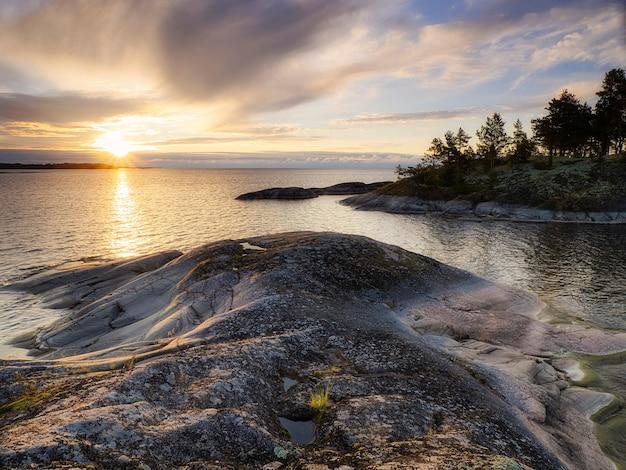 Cichy wschód słońca nad skalistym brzegiem. jezioro ładoga. republika karelii, rosja
