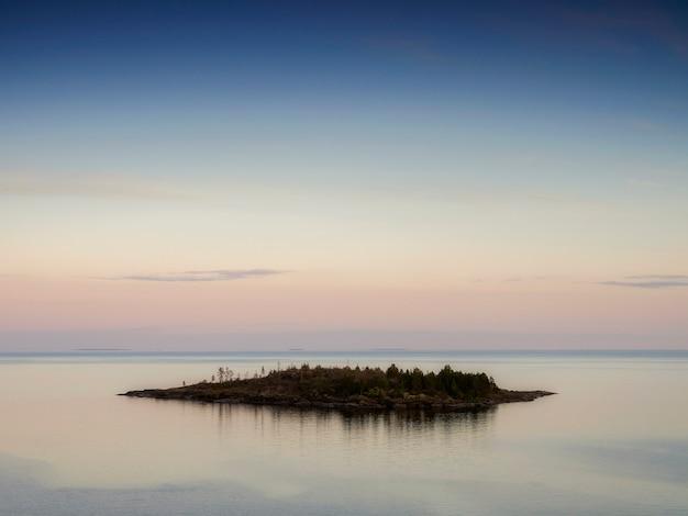 Cichy zachód słońca nad małą wyspą. jezioro ładoga. republika karelii, rosja