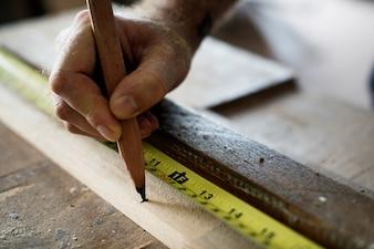 Cieśla używa ołówek i pomiar taśmy na drewnie