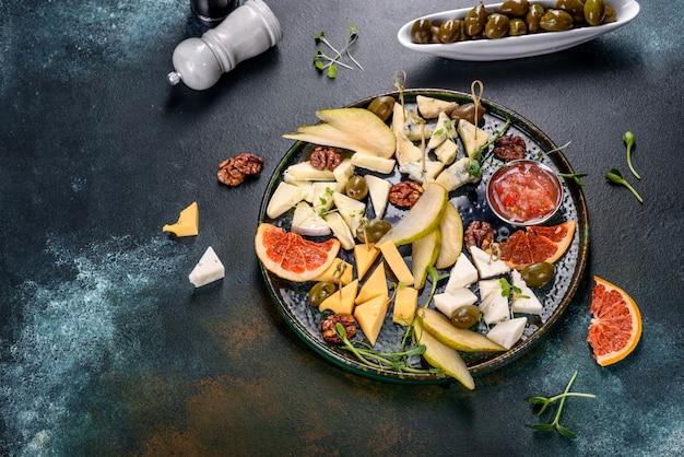 Cięcie czterech rodzajów sera: koziego, parmezanu, camemberta i brie z gruszką oraz plastrami suszonego grejpfruta i mikro zieleniną. smaczna zdrowa przekąska