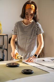 Cięcie i szycie w studiu krawieckim młoda kobieta pracuje z tkaniną w studiu projektowym