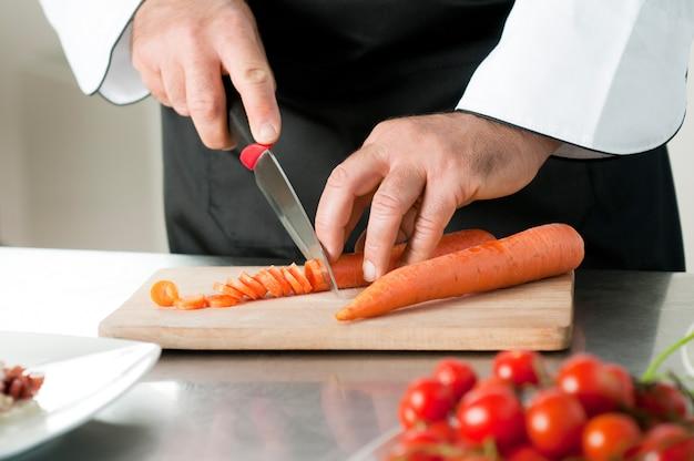 Cięcie marchewki na desce do przygotowania posiłku w restauracji