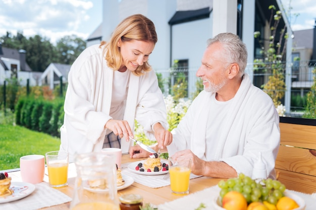 Cięcie naleśników. kochająca przystojna żona czuje się niesamowicie krojąc dla męża poranne naleśniki z owocami