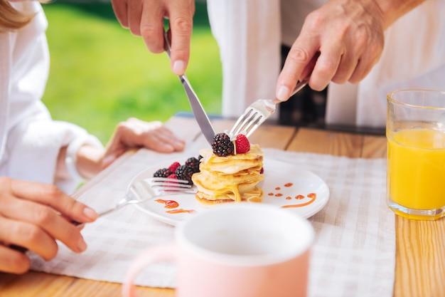 Cięcie naleśników. kochający, troskliwy mąż kroi naleśniki z owocami i miodem na wierzchu dla żony jedzącej śniadanie na tarasie