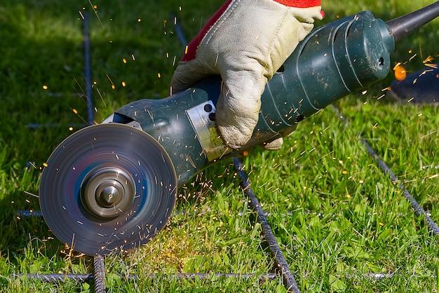 Cięcie siatki metalowej za pomocą młynka na zielonej trawie. iskry z materiałów kontaktowych. pracownik na zewnątrz, przeciąć stalową siatkę. proces za pomocą szlifierki kątowej.